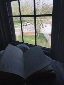 Mindy reading a book while overlooking the quad.